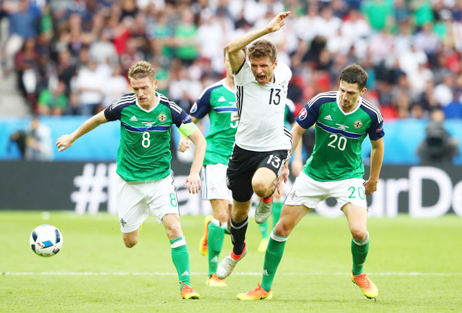 Germany's Thomas Mueller (centre) is challenegd by Northern Ireland's Steven Davis (left) and Craig Cathcart (right)