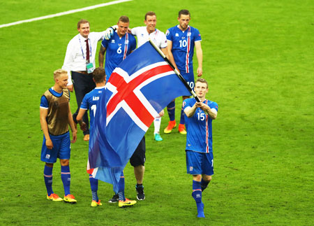 Iceland's Jon Dadi Bodvarsson leads celebrations with his national flag after victory over Austria in the Euro 2016 Group F match at Stade de France in Paris on Wednesday
