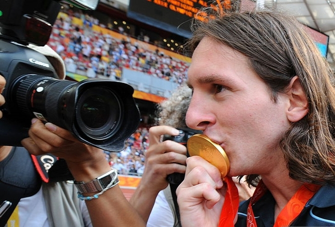 Argentinian forward Lionel Messi kisses his gold medal as he leaves the pitch after attending the men's Olympic football tournament medal ceremony at the national stadium in Beijing during the 2008 Beijing Olympic games on August 23, 2008