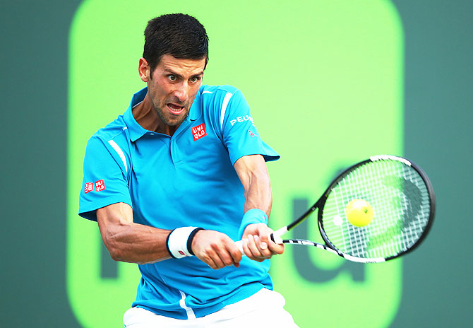 Serbia's Novak Djokovic plays a backhand against Portugal's Joao Sousa in their third round match at the Miami Open at Crandon Park Tennis Center in Key Biscayne, Florida, on Sunday