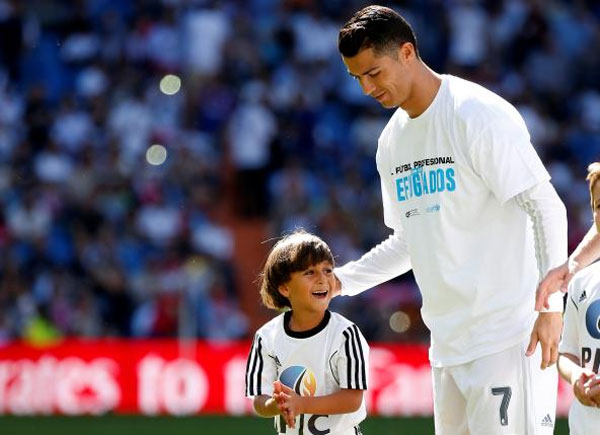 Zaid, son of Osama Abdul Mohsen, smiles as he stands next to Real Madrid's Cristiano Ronaldo before the Spanish first division soccer match against Granada at Santiago Bernabeu stadium in Madrid, on September 20, 2015
