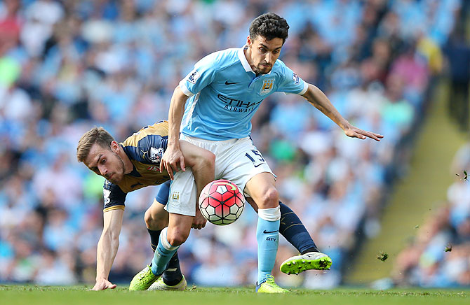 Manchester City's Jesus Navas holds off a challenge by Arsenal's Aaron Ramsey during their Barclays English Premier League match at the Etihad Stadium in Manchester on Sunday