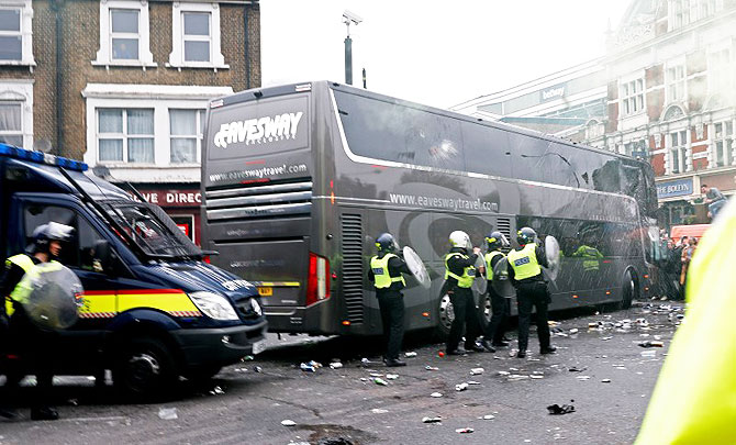 Police get into action as bottles are thrown at the Manchester United team bus before the match