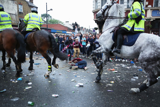 A man is knocked over by police horses as West Ham fans become violent and start throwing bottles at police outside the Boleyn Ground