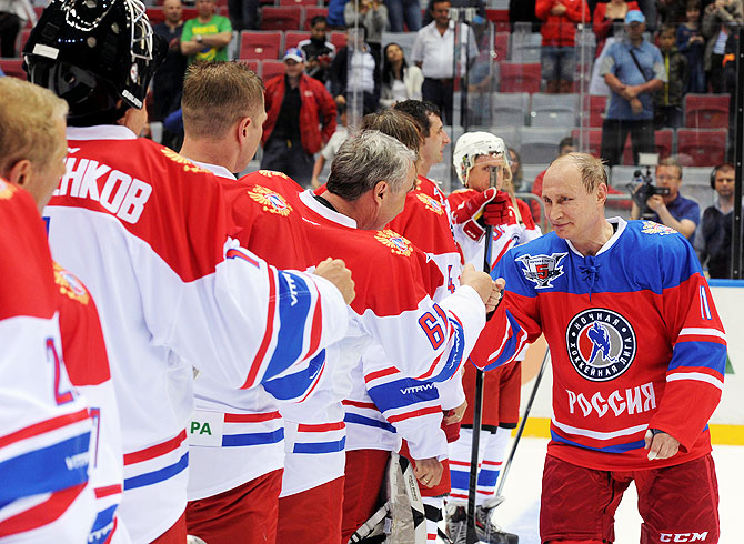Russian President Vladimir Putin greets participants of a gala game of the Night Ice Hockey League