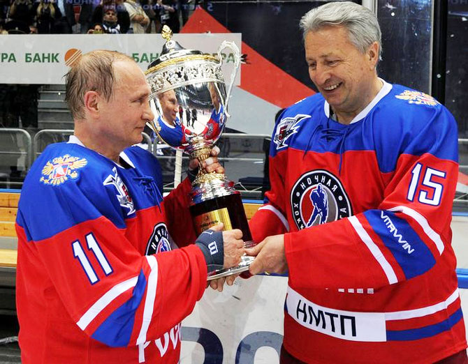 Russian President Vladimir Putin and Soviet former player Alexander Yakushev hold a trophy as they take part in a gala game of the Night Ice Hockey League on Tuesday