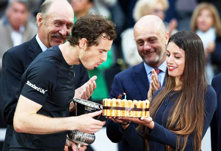 Andy Murray blows out candle on his birthday cake after winning the match against Novak Djokovic to win the Italian Open on Sunday