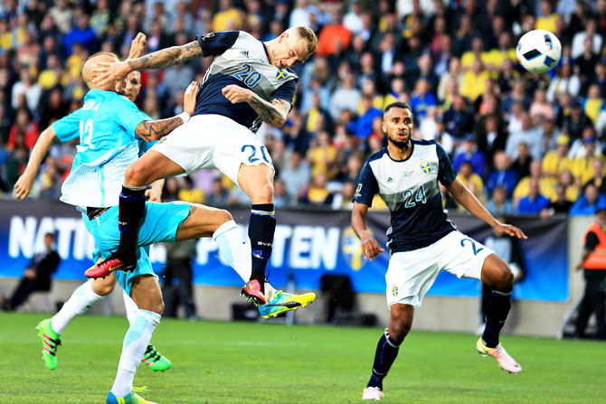 Sweden's John Guidetti heads a ball away from a Slovenian player as teamate Isaac Kiese Thelin watch duirng their international friendly in Malmo, on Monday
