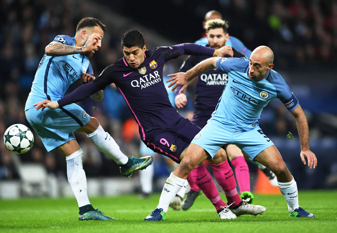 Barcelona's Luis Suarez (centre) is tackled by Manchester City's Nicolas Otamendi (Left) and Pablo Zabaleta