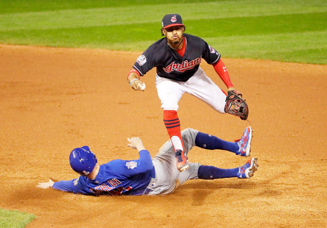 Francisco Lindor #12 of the Cleveland Indians jumps over Chris Coghlan #8 of the Chicago Cubs as Coghlan is out at second base