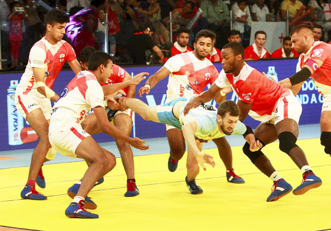 England players try to catch a player of Argentina during Kabaddi World Cup match in Ahmedabad on Friday
