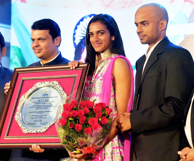 Maharashtra Chief Minister Devendra Fadnavis felicitates Olympic silver medallist shuttler P V Sindhu and her coach Gopichand in Mumbai on Tuesday