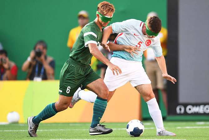 Tiago of Brazil (left) competes for the ball with Recep Aydeniz of Turkey (right) in the men's football 5-a-side on Sunday, September 11