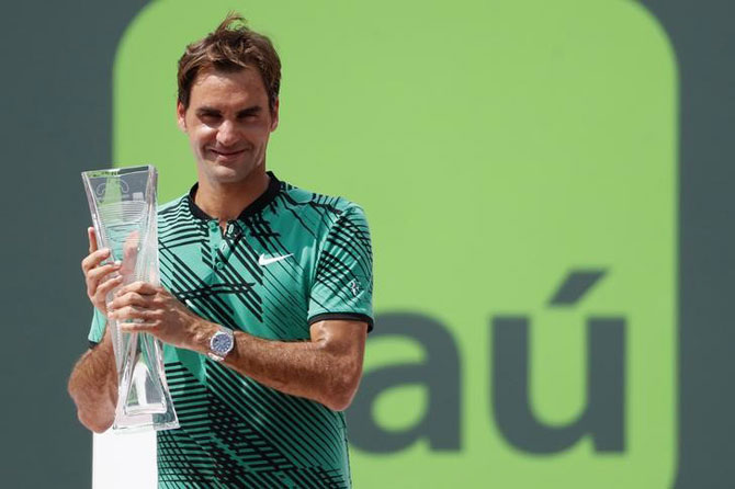 Switzerland's Roger Federer holds the Butch Buchholz trophy after beating Spain's Rafael Nadal to win the Miami Open title at Crandon Park Tennis Center in Key Biscayne, Florida, on Sunday