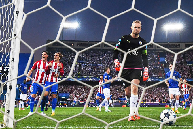 Atletico de Madrid's Antoine Griezmann celebrates with teammate Fernando Torres after scoring from  the penalty spot as Leicester City's Kasper Schmeichel retrieves the ball from the net during their UEFA Champions League quarter-final first leg match at Vicente Calderon Stadium in Madrid on Wednesday