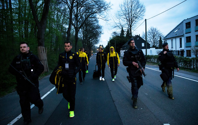 (Left-Right) Borussia Dortmund's Sven Bender, Marcel Schmelzer and Nuri Sahin are escorted to a car by police after the team bus of the Borussia Dortmund was damaged in an explosion in Dortmund, Germany, on Tuesday