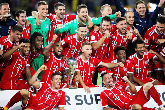 Bayern Munich players celebrate with the trophy after winning the DFL-Supercup Final
