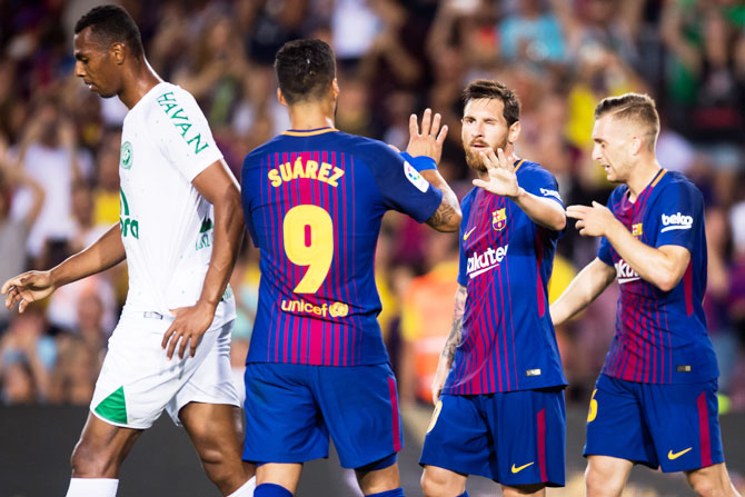 FC Barcelona's Lionel Messi celebrates with his teammates Luis Suarez (left) and Gerard Deulofeu (right) after scoring his team's third goal