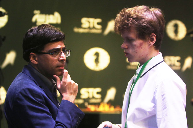 Chess players Vladislav Artemiev (right) and Viswanathan Anand speak on the Day 6 of the King Salman Rapid & Blitz Chess Championships in Riyadh, Saudi Arabia on Saturday