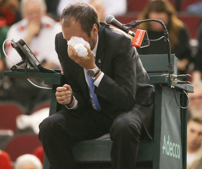 Chair umpire Arnaud Gabas reacts to getting hit in the eye with a ball hit by Denis Shapovalov of Canada