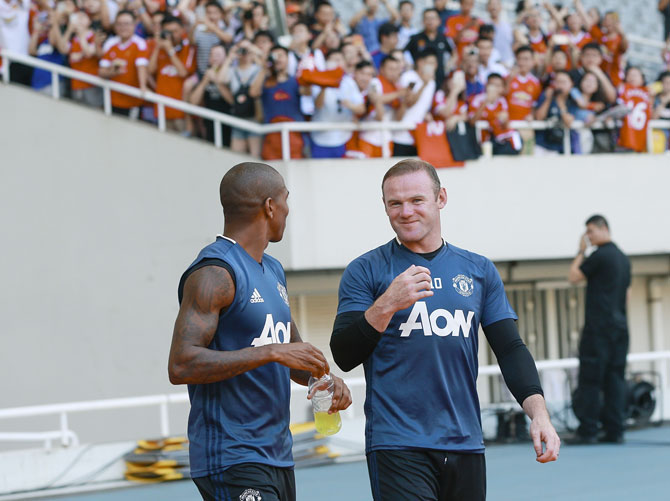 Frenzied fans click pictures (blurred background) of Manchester United's Ashley Young and Wayne Rooney during the team training session at their pre-season tour of China at Shanghai Stadium in Shanghai on July 21, 2016