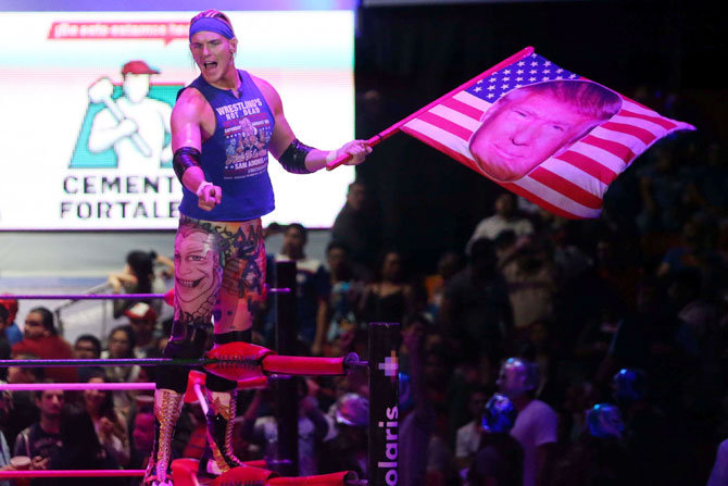 US wrestler Sam Adonis, 27, role-playing as a fan of US President Donald Trump, waves a flag with Trump's face during a wrestling fight at the Coliseo Arena in Mexico City, Mexico, on Sunday