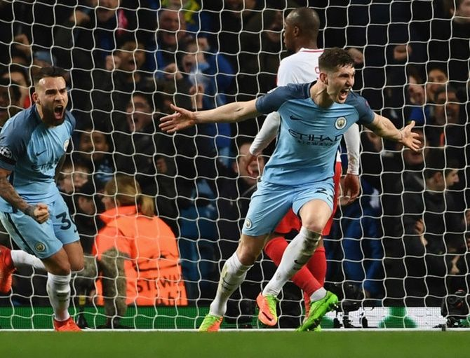 Manchester City's John Stones (right) says he is 'developing as a player and a person under Guardiola'