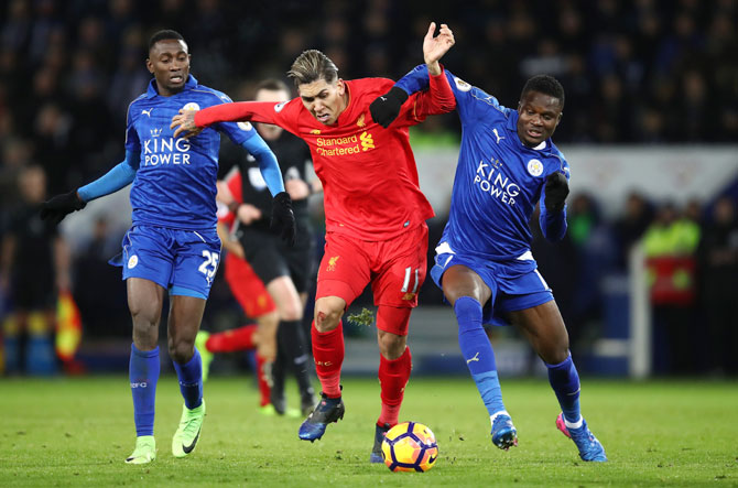 Liverpool's Roberto Firmino  holds off Leicester City's Daniel Amartey (right) and Wilfred Ndidi as they vie for possession