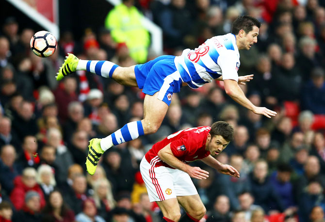 Reading's Yann Kermorgant goes airbone in a challenge against Manchester United's Michael Carrick