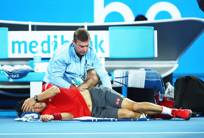 Kei Nishikori receives treatment from the physio during an injury time out in his fourth round match against Roger Federer