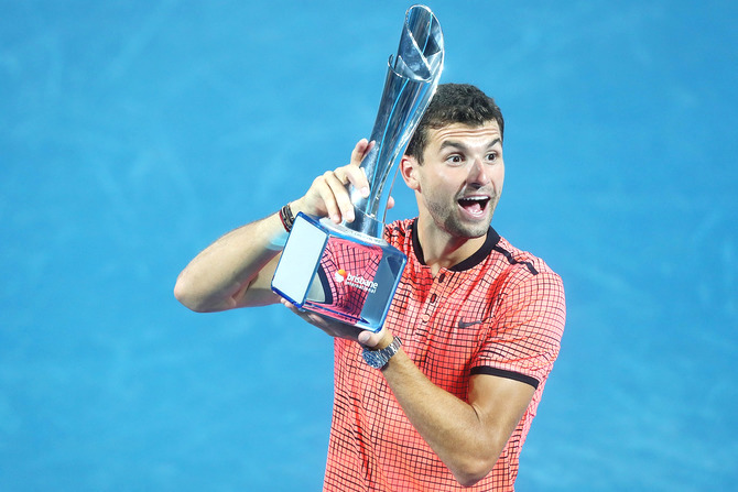 Bulgaria's Grigor Dimitrov holds the Roy Emerson trophy after defeating Japan's Kei Nishikori to win the men's final of the Brisbane international at Pat Rafter Arena in Brisbane, on Sunday