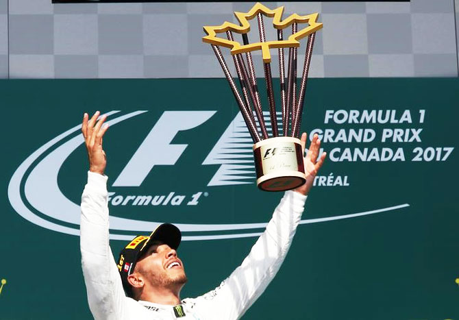 Mercedes' Lewis Hamilton celebrates with the trophy after winning the Canadian F1 GP in Montreal, Quebec on Sunday