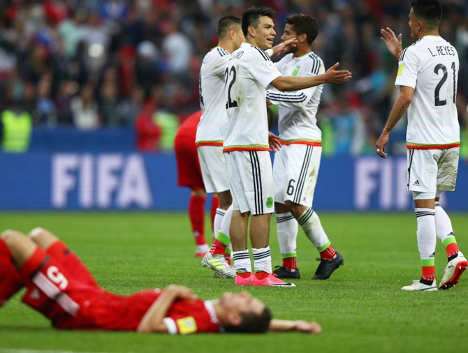 Mexico players celebrate their 2-1 victory while Viktor Vasin of Russia shows dejection