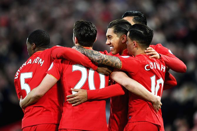 Liverpool's Roberto Firmino (right) celebrates with teammates on scoring his side's first goal against Arsenal during their Premier League match at Anfield in Liverpool on Saturday