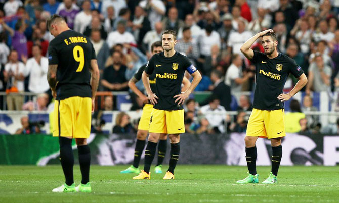 Atletico Madrid's Fernando Torres, Gabi and Koke look dejected after Real Madrid's third goal during their Champions League semi-final first leg match at the Santiago Bernabeu in Madrid on Tuesday