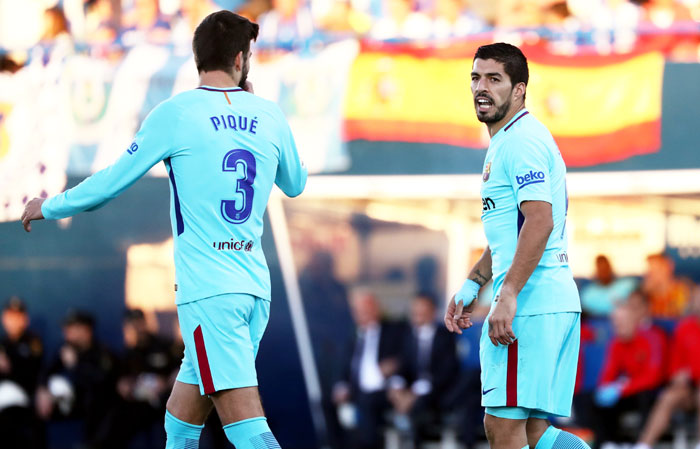 Gerard Pique and Luis Suarez (right) received cards during their La Liga match against Leganes on Saturday