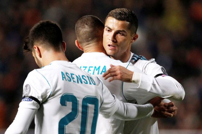 Real Madrid's Karim Benzema celebrates scoring their fourth goal with teammates Cristiano Ronaldo and Marco Asensio during their Champions League match against APOEL Nicosia at GSP Stadium in Nicosia, Cyprus on Tuesday