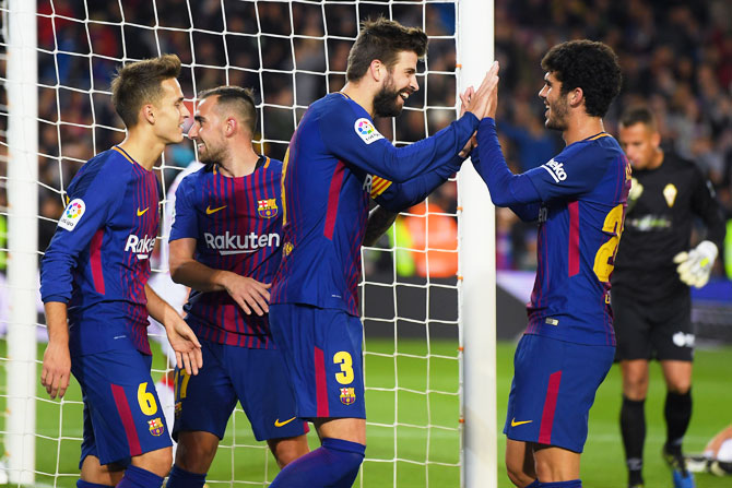 FC Barcelon's Gerard Pique (centre) celebrates with his teammates after scoring his team's second goal against Real Murcia during the Copa del Rey round of 32 second leg match at Camp Nou in Barcelona on Wednesday