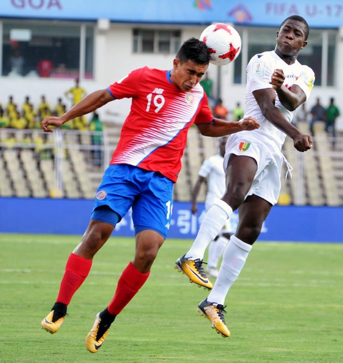 Players of  Costa Rica and Guinea vie for the ball