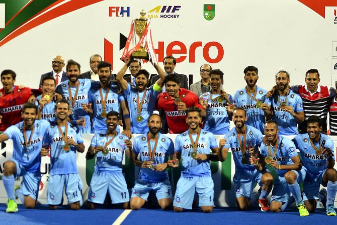 India's players celebrate with the Asia Cup after beating Malaysia in the final