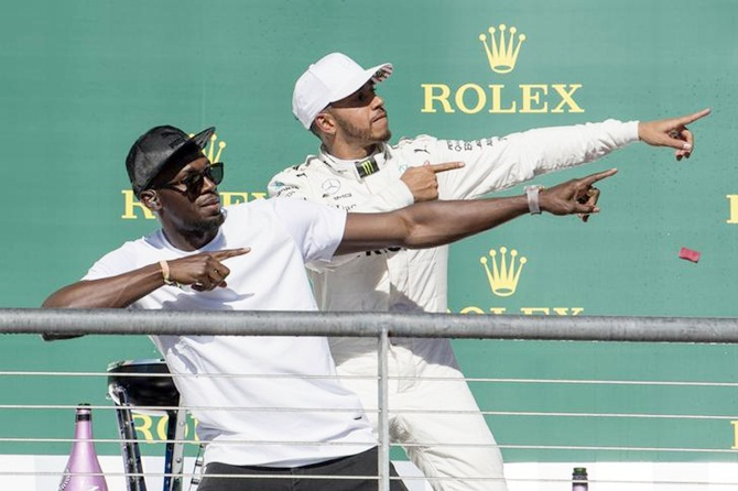 Mercedes driver Lewis Hamilton of Great Britain poses with Olympic sprint champion Usain Bolt after winning the United States Grand Prix at the Circuit of the Americas.