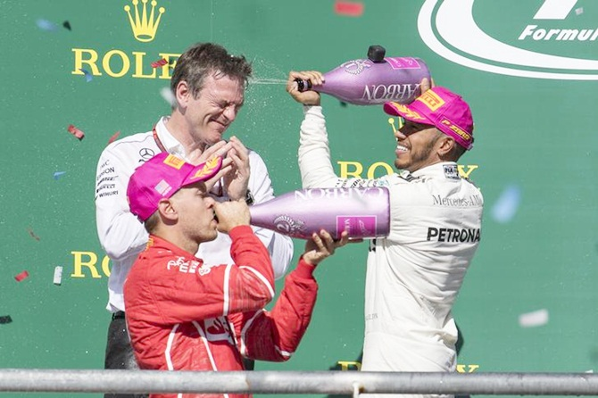 Mercedes driver Lewis Hamilton pours champagne on Mercedes technical director James Allison as Ferrari driver Sebastian Vettel (5) sips the bubbly on the podium after the United States Grand Prix.