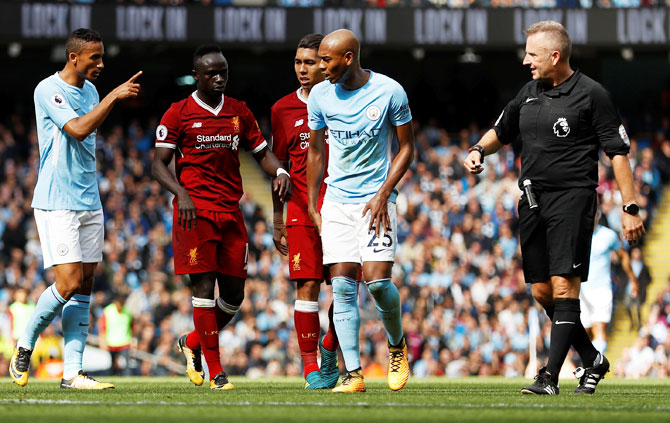 Liverpool's Sadio Mane (2nd from left) walks off the pitch after receiving the red card from referee Jon Moss for crashing into and injuring Manchester City keeper Ederson while going for a high ball during  their English Premier League match in Manchester on Saturday