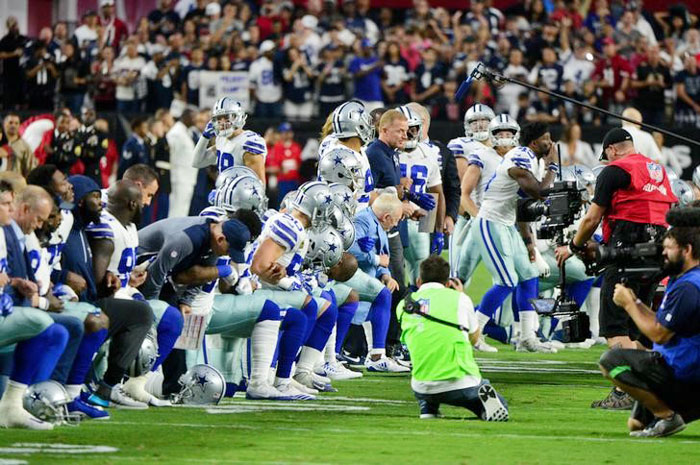 The Dallas Cowboys players, coaches staff and owner Jerry Jones take a knee prior to the National Anthem before the game against the Arizona Cardinals at University of Phoenix Stadium on Monday