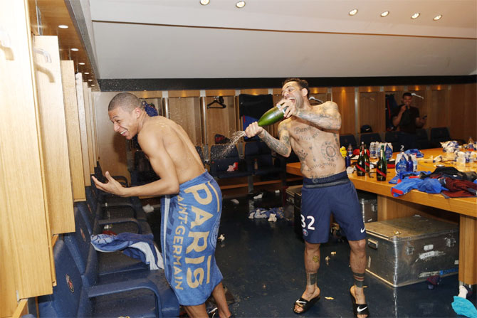 PSG's Kylian Mbappe and Dani Alves (right) celebrate in the dressing room after their title win