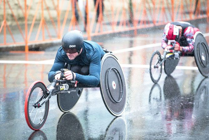 Wheelchair racers spray rain from their wheels as they make their way towards the 24th mile of the 2018 Boston Marathon on Monday