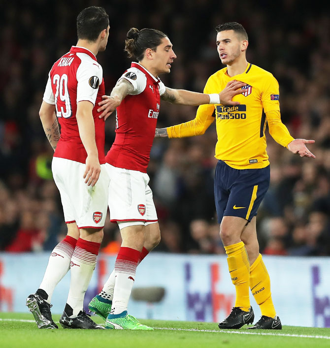 Arsenal's Granit Xhaka and Atletico Madrid's Lucas Hernandez are restrained as they clash