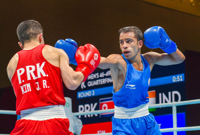 India's Amit Panghal (Blue) and PR Koreas Ryong Jong compete in the Men's Light Fly (46-49kg) Quarter-final boxing event in the 18th Asian Games 2018 in Jakarta, Indonesia on Wednesday
