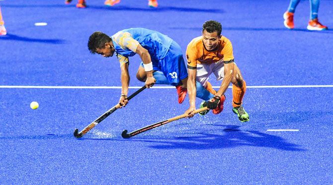 India's Vivek Prasad (left) and a Malaysian player in action during the men's hockey semi-final match at the 18th Asian Games 2018, in Jakarta, Indonesia on Thursday