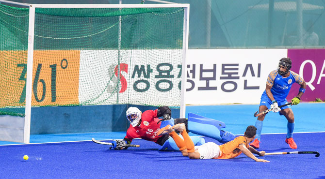 India's captain and goalkeeper Sreejesh saves a goal during the Asian Games hockey semi-final match against Malaysia